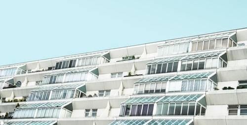 Bild på vita etage-lägenheter under blå himmel
