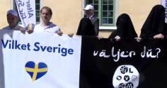 """Bild på två svenskar som håller en vit flagga med texten """"Vilket Sverige"""" och AfS symbol (Svenska flaggan i ett hjärta) till vänster, samt tre varelser i svarta burqas till höger med en svart flagga med texten """"väljer du?"""" samt de åtta riksdagspartiernas symboler tillsammans likt en IS-flagga."""