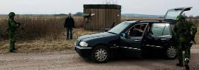 Bild på militärer som undersöker en misstänkt bil och håller föraren under uppsikt med automatvapen.