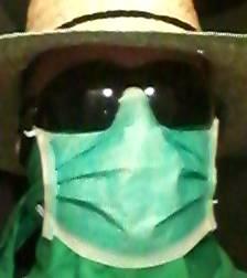 Bild på individ i stråhatt, heltäckande solglasögon och munskydd.