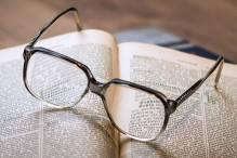 Bild på glasögon på öppen bok