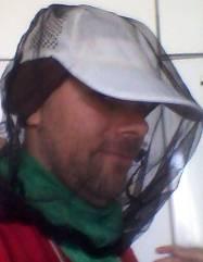 Bild på bärplockare iförd huvudduk, keps, myggnät och schal runt nacken