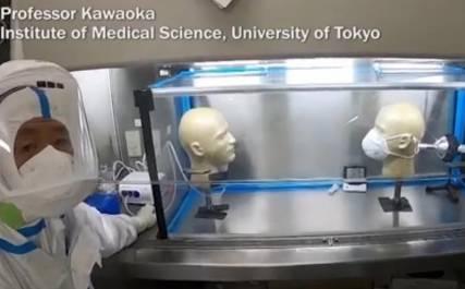 Bild på Professor Kawaoka i lab med testutrustning inklusive ansiktsmask